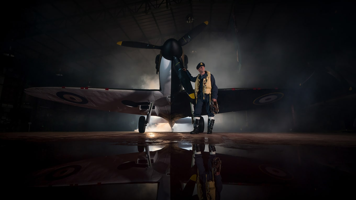 terry-donnelly-sony-alpha-9-pilot-poses-next-to-old-fashioned-plane-with-strong-backlight